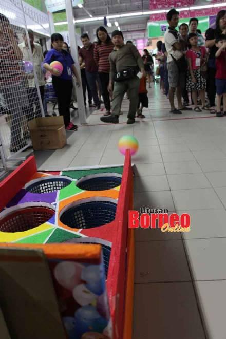 Para pengunjung mencuba kemahiran mereka dalam permainan 'Ball Shooting' di salah sebuat pasar raya Emart.