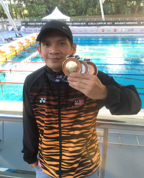 Atlet renang para kebangsaan Jamery Siga menunjukkan pingat yang dimenanginya pada Sukan Para ASEAN 2017.