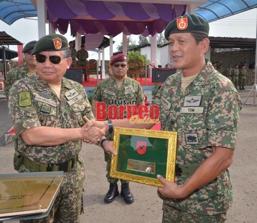 Ahmad Hasbullah (kiri) menyerahkan plak bendera 13 Briged kepada Panglima 13 Briged Brigadier Jeneral Datuk Arman Rumaizi Ahmad semasa penstrukturan semula 13 Briged baru-baru ini.