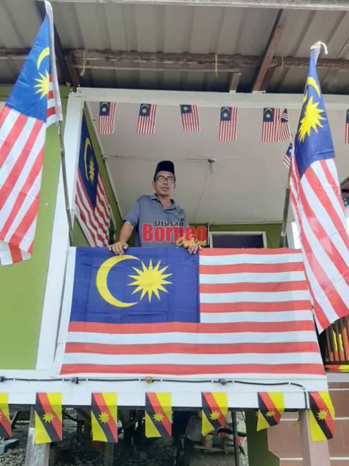 Malaysia Sahat dari Kampung Endap berdiri di anjung rumahnya yang dihiasi dengan warna-warni bendera yang menunjukkan semangat patriotiknya.