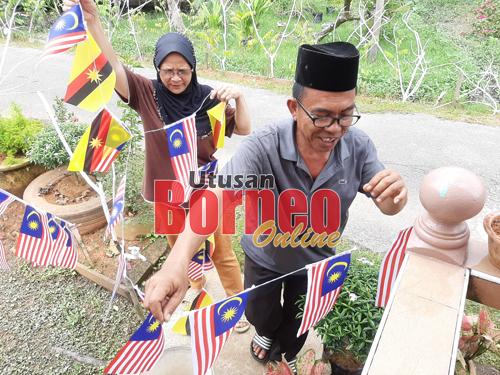 Malaysia ditemani Fatimah menggantung lebih banyak bendera di halaman rumahnya