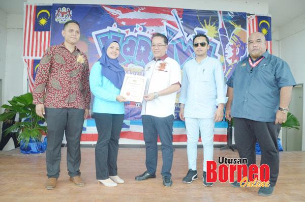 Liew (tengah) menyampaikan sijil penghargaan kepada wakil sebuah agensi yang menyertai Karnival Merdeka Jom Cari Kerja.