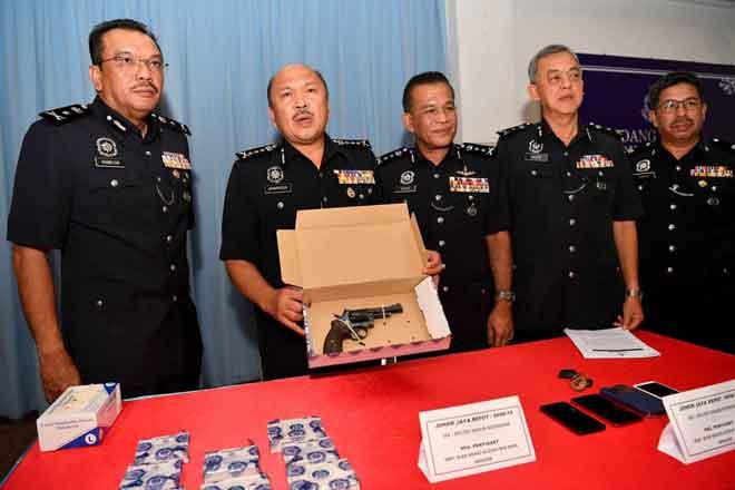 Mohd Kamarudin menunjukkan sepucuk pistol jenis Revolver dan sebutir peluru hidup yang dirampas selepas anggotanya berjaya menahan tiga suspek yang dipercayai terlibat dalam kes samun bersenjata dan bunuh pada sidang media di Ibu Pejabat Polis Daerah Seri Alam, Johor Bahru semalam. — Gambar Bernama