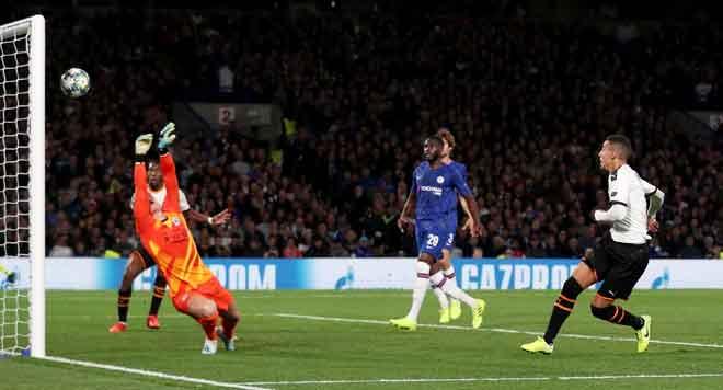 Rodrigo (kanan) menyaksikan bola rembatannya gagal ditepis oleh Kepa sebelum menerjah jaring untuk gol pertama Valencia pada perlawanan di Stamford Bridge, London kelmarin. — Gambar AFP
