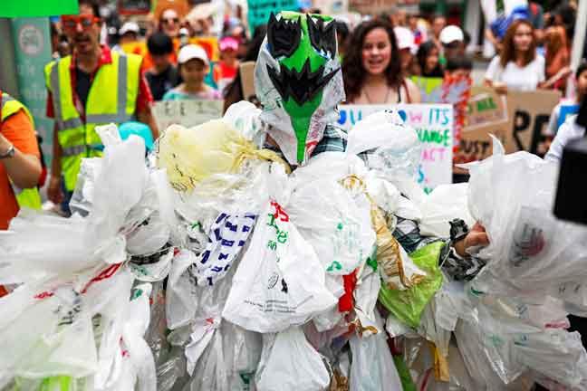 Seorang aktivis alam sekitar kelihatan memakai kostum diperbuat daripada beg plastik, ketika menyertai jutaan kanak-kanak di seluruh dunia yang melancarkan mogok iklim global, berhampiran pejabat Kementerian Alam Sekitar dan Sumber Asli di Bangkok, Thailand semalam. — Gambar Reuters