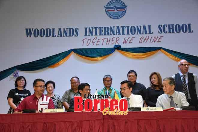 Dr Annuar (bediri tengah) ngemata Dr Ahmad (duduk, dua ari kiba) enggau Tiong (duduk, dua kanan) bela betukar MoU, lalu dikemataka bala bukai.