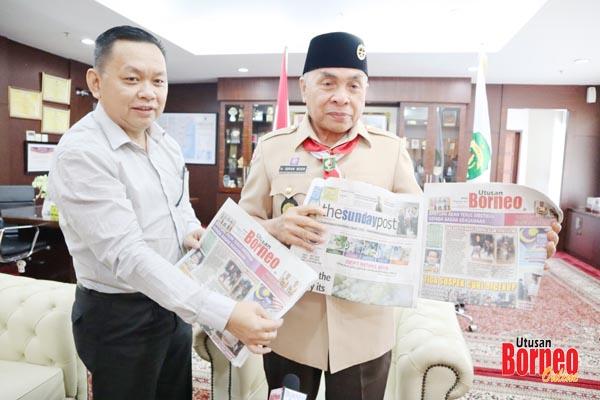 Isran Noor menatap akhbar Utusan Borneo dan The Borneo Post, sambil diberi penerangan oleh Lichong (kiri).