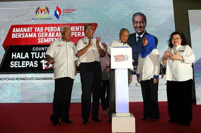 Tun Dr Mahathir Mohamad (tengah) melakukan gimik perasmian pada Majlis Amanat Bersama Gerakan Koperasi dan Sambutan Suruhanjaya Koperasi Malaysia (SKM) serta Majlis Countdown Halatuju Koperasi pada 2022 di Tamarind Square semalam. — Gambar Benama