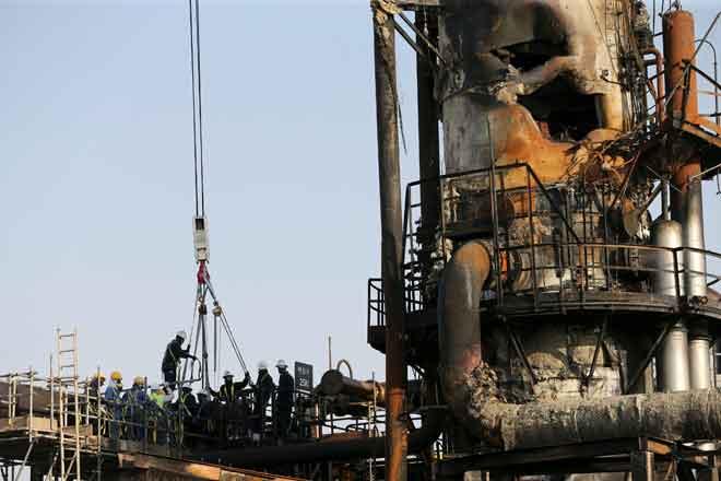 Pekerja dilihat membaiki kerosakan di kemudahan minyak Aramco di Abqaiq, Arab Saudi kelmarin. — Gambar Reuters