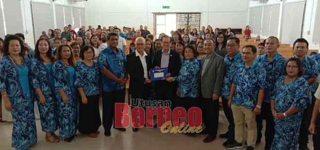 Lee (tujuh kiri) menyampaikan cek bernilai RM250,000 daripada UNIFOR kepada Gereja Methodist Iban Miri di Lutong semalam.