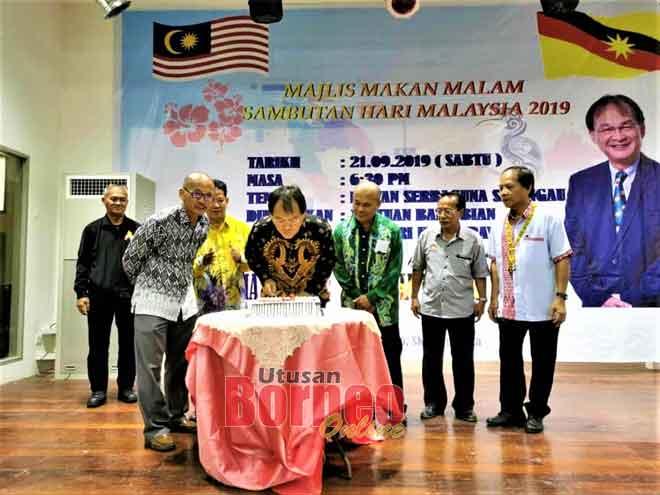 Baru (empat kanan) serta yang lain ketika meraikan Majlis Makan Malam Sambutan Hari Malaysia di Selangau, kelmarin.