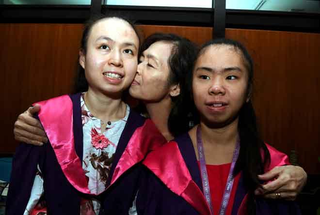 Teresa Wong mencium Felicia yang akan menerima pingat emas Universiti Sains Malaysia (USM) bagi pelajar kelainan upaya pada Majlis Konvokesyen USM ke-57 yang bermula esok pada sidang akhbar semalam. — Gambar Benama