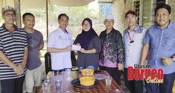 Arunarnsin menyampaikan sumbangan kepada keluarga yang terlibat dalam kejadian angin kencang di Kampung Jaya Bakti.