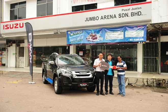 Pengurus Besar Isuzu Malaysia, Kenkichi Sogo menyerahkan hadiah kepada Sugumaran di bilik pameran Isuzu Jumbo Arena, di Kluang.