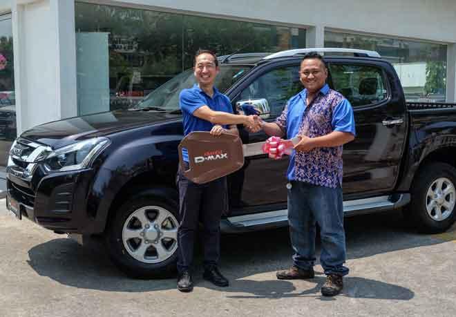 Ketua Pegawai Operasi Isuzu Malaysia, Masayuki Suzuki menyerahkan hadiah yang dimenangi Ghanie di bilik pameran Isuzu KM Mobil di Bintulu.
