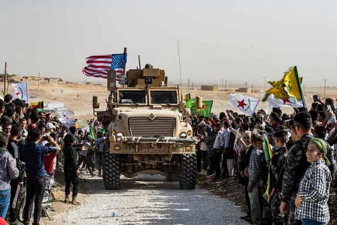 Penduduk Kurdis Syria mengerumuni sebuah kereta perisai tentera AS semasa mengadakan demonstrasi mengecam ancaman Turki berdekatan pangkalan tentera pakatan antarabangsa diketuai AS di pinggir bandar Ras al-Ain dalam wilayah Hasakeh dekat sempadan dengan Turki, semalam. — Gambar AFP