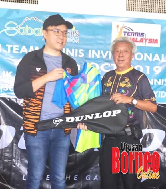 Johnson (kanan) menyampaikan cenderahati berupa baju dan raket tenis kepada Phoong.