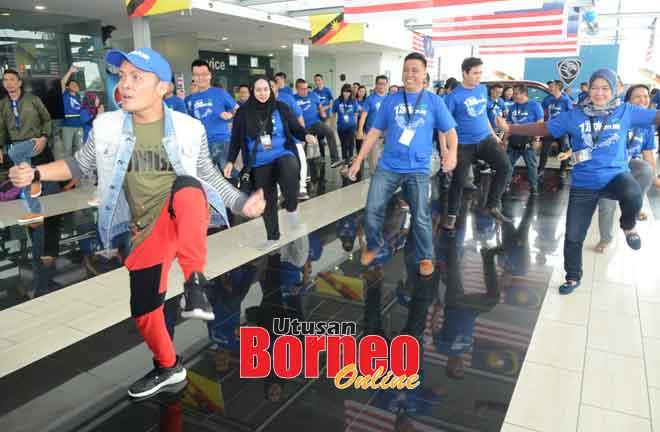 Para peserta Proton 1 Tank Adventure melakukan aktiviti zumba di Proton Edar Kuching Jalan Tun Jugah.