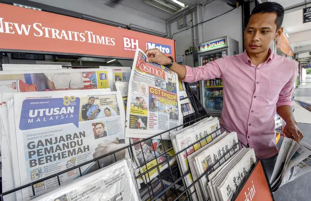 Syazwan Zaki, 28, mendapatkan akhbar Kosmo dan Utusan Malaysia yang merupakan keluaran terakhir selepas Utusan Melayu (M) Bhd menamatkan operasi perniagaannya berkuat kuasa hari ini. - Gambar Bernama