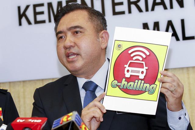 Loke menunjukkan pelekat kenderaan e-hailing semasa sidang media di kementeriannya hari ini. - Gambar Bernama