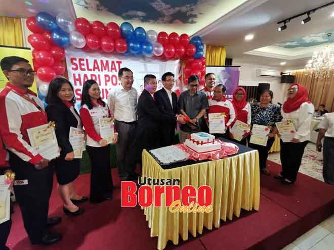 Bong (lima kiba), Adiman (tujuh kanan), Abang Sardon (enam kanan) enggau bala staf Pos Malaysia ke bulai deka melah kek dikena ngerami Hari Pos Sedunya 2019 Renggat Sarawak, kemari.
