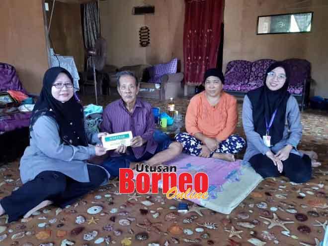 Marini (kiri) menyampaikan sumbangan TBS kepada Pagis (dua kiri) selepas rumah miliknya ranap dijilat api malam kelmarin.