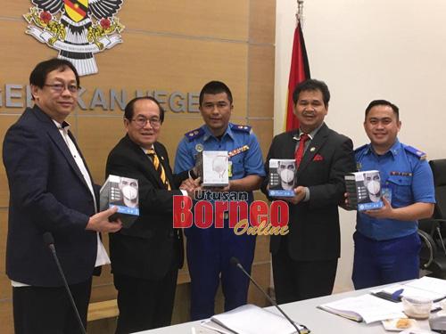 Uggah menyerahkan topeng muka kepada APM Negeri Sarawak selepas mesyuarat JPBN (Monsun Timur Laut) hari ini