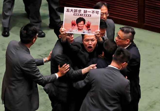 Penggubal undang-undang prodemokrasi diheret keluar oleh pengawal keselamatan ketika Lam menjawab soalan daripada penggubal undang-undang berhubung dengan ucapan dasarnya di dewan undangan di Hong Kong, China semalam. — Gambar Kim Kyung-Hoon/Reuters