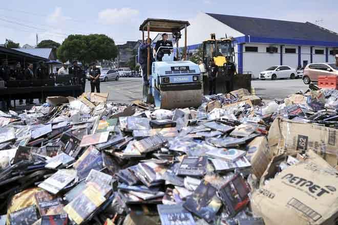 Ahmad memandu sebuah jentera berat untuk memusnah dan melupuskan lebih 50,000 keping cakera padat digital (DVD) cetak rompak dan lucah di IPD Kajang, Kajang semalam. — Gambar Bernama
