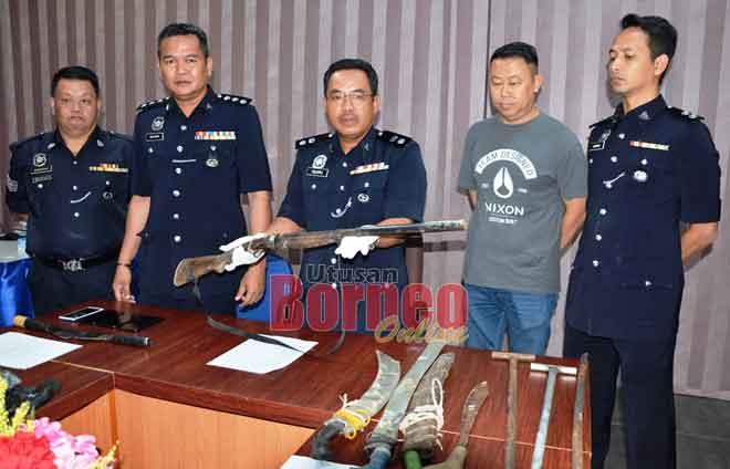 ZuLkipli (tengah) menunjukkan senapang buatan sendiri yang dirampas daripada suspek.