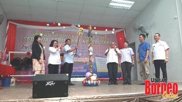 Masiung melancarkan Sambutan Hari Warga Emas Sedunia Peringkat Negeri Sabah sambil diperhatikan oleh Christina (dua kiri).