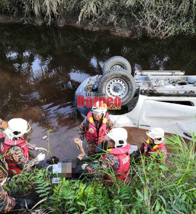 Anggota bomba berusaha mengangkat mayat mangsa ke permukaan jalan raya