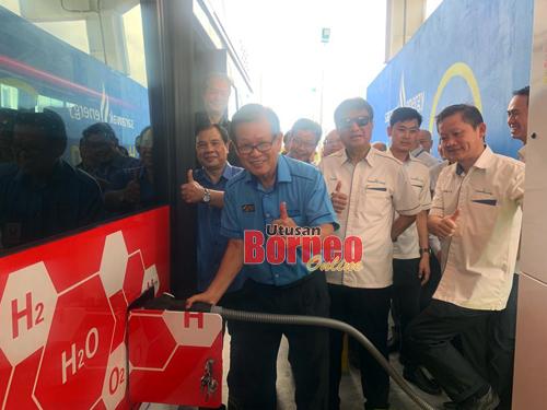 Lee mengisi gas hidrogen dalam tangki bas. Turut kelihatan, Dr Jerip dan Sharbini. Gambar oleh Chimon Upon