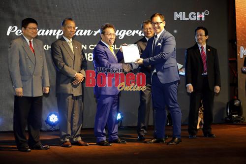 Dr Sim ditemani Penguang (dua kiri) dan tetamu kehormat lain menyampaikan Anugerah Perkhidmatan Cemerlang kepada penerima, Dr Cheong Yaw Liang.