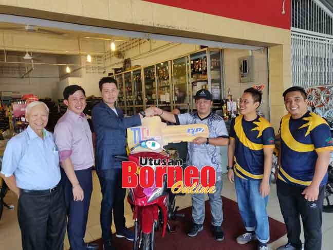 Alan (tiga kiri) menyerahkan kunci replika kepada Ketua Stesen RTM Miri Zaidi Bujang tanda simbolik penyerahan motosikal untuk pemenang bertuah ACSJ.
