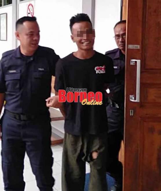 Tertuduh (tengah) dibawa keluar dari Mahkamah Sesyen setelah dijatuhkan hukuman.