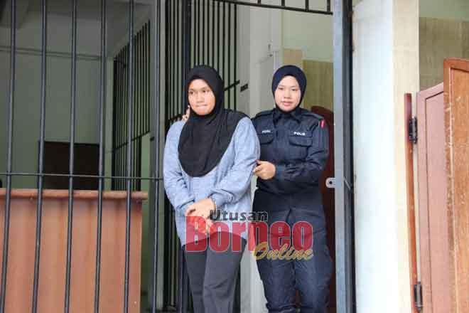 Tertuduh (kiri) dibawa keluar dari mahkamah.