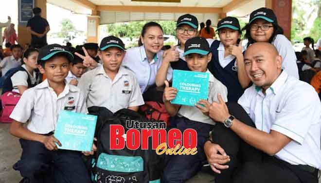 Zulaihi (kanan) serta kakitangan Petronas merakam gambar bersama murid yang menerima sumbangan daripada Yayasan Petronas, kelmarin.