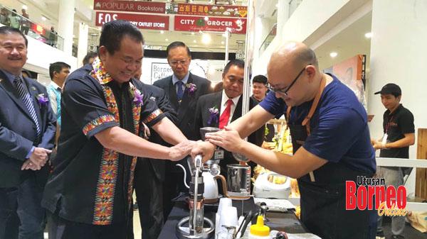 Seorang barista menunjukkan kepada Madiyem proses menyediakan kopi sambil diperhatikan oleh Chong.