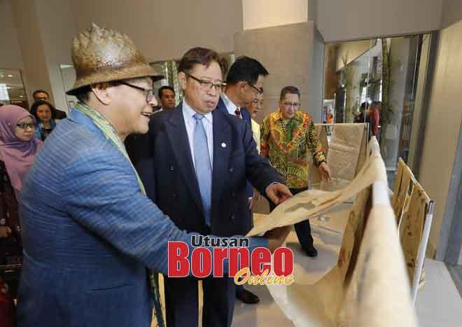 Abang Johari melihat salah satu tekstil yang dipamerkan sempena Forum Kraf di Kampus Muzium Sarawak, semalam. Turut kelihatan Edric (kiri). — Gambar Chimon Upon