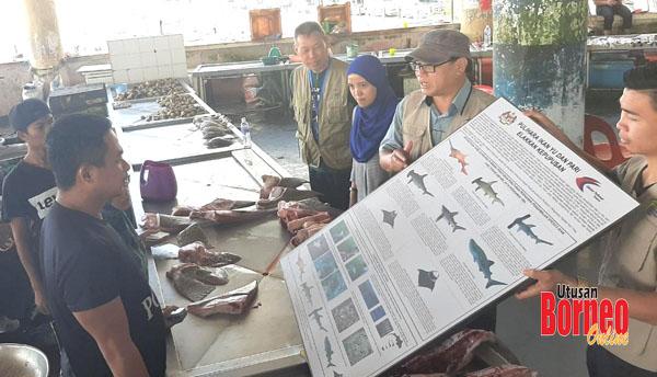 Lawrence (dua kanan) memberi penerangan kepada penjual ikan berhubung spesies baharu ikan yang dilindungi sambil diperhatikan oleh Norainon (tiga kanan).