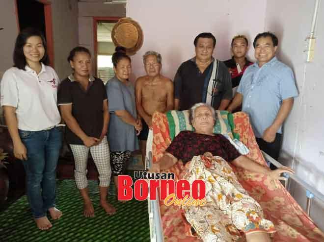 Menai (berbaring) menerima bantuan katil boleh laras daripada ADUN Repok, Dato Sri Huang Tiong Sii.