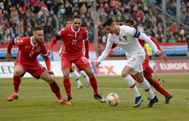 Ronaldo (dua kanan) ketika bersaing dengan pemain Luxembourg pada perlawanan di Stadium  Josy Barthel, Luxembourg kelmarin. — Gambar AFP