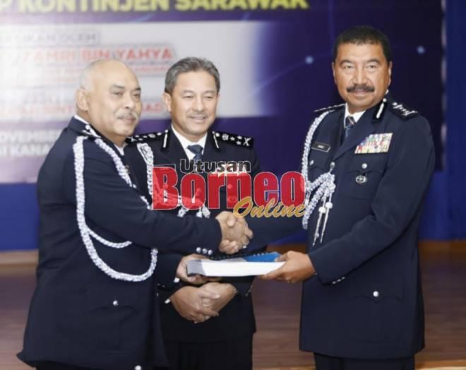 Ramli (kanan) dan Azman bertukar dokumen serah terima tugas sebagai Pesuruhjaya Polis Sarawak baharu sambil disaksi Zamri.