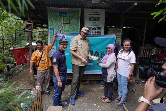 Pengusaha madu kelulut Rosmiah Kantilik (dua kanan) menerima cenderahati daripada Sallehhuddin (tengah) semasa lawatan ke Taman Kelulut Eraros Kampung Kinapulidan Ranau.
