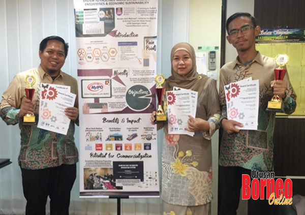 Dr Imbarine, Mariam dan Ahmad Fauze memegang trofi dan sijil kemenangan disebelah aplikasi inovatif mereka.