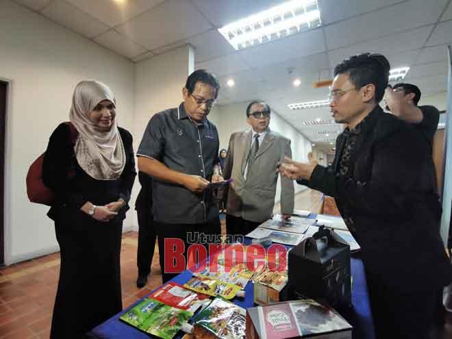 Dr Abdul Rahman (tengah) melihat beberapa sampel pembungkusan produk di sebuah reruai di luar dewan seminar. Turut kelihatan Abang Abdul Karim (di sebelah kiri beliau) dan Sarimah.