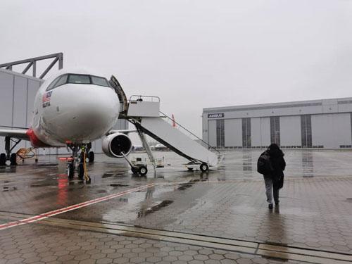 Penumpang berjalan ke arah pesawat di landasan Airbus