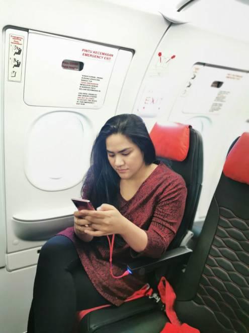 Farhana melihat sambil mengecas telefon pintarnya pada USB di tempat duduk penumpang.