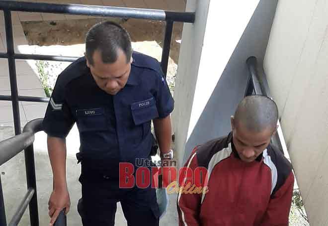 Tertuduh semasa menuju ke bilik tahanan Mahkamah Kuching.